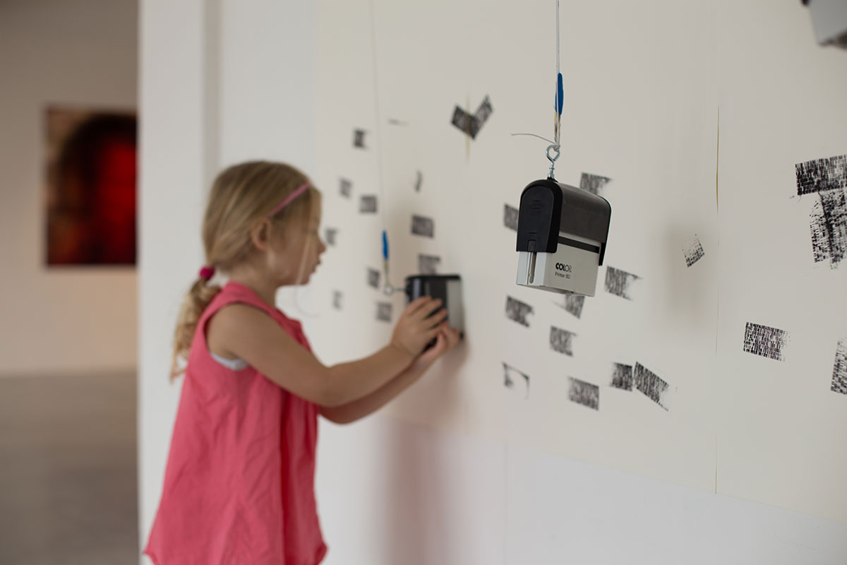 A girl stamping one of the first patterns on the wall.